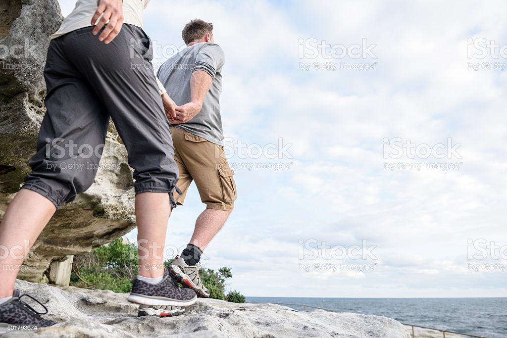 Mature couple hiking on rocks holding hands, Bondi Beach stock photo
