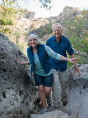 Mature couple hiking through large boulders