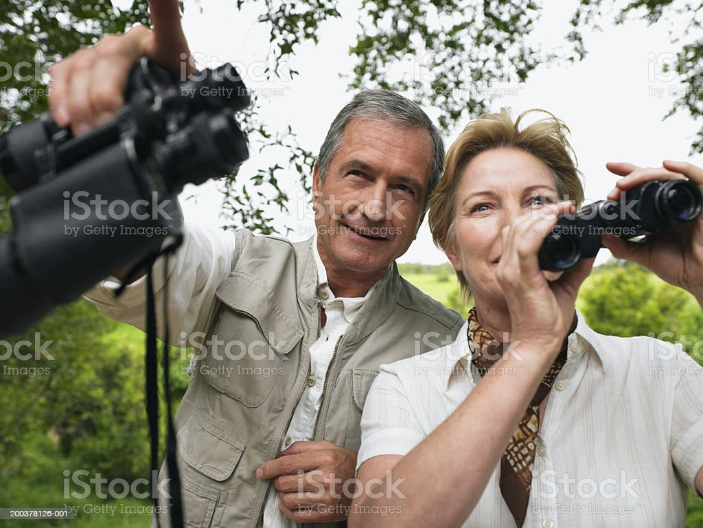 Mature couple holding binoculars, man pointing ahead, smiling royalty-free stock photo