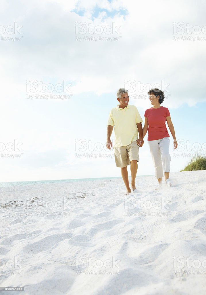 Mature couple holding hands while walking on a beach royalty-free stock photo