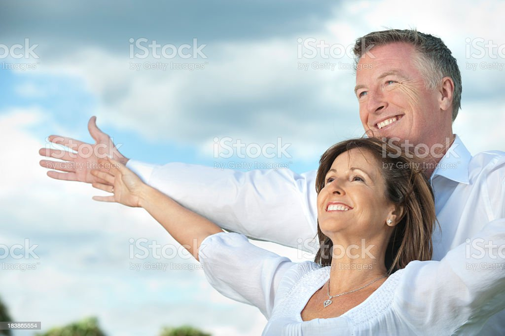 Mature couple holding out their arms royalty-free stock photo
