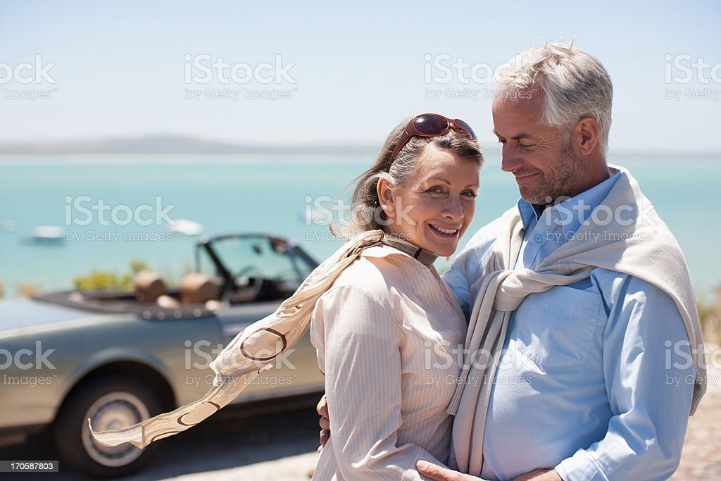 Mature couple hugging at waterfront royalty-free stock photo