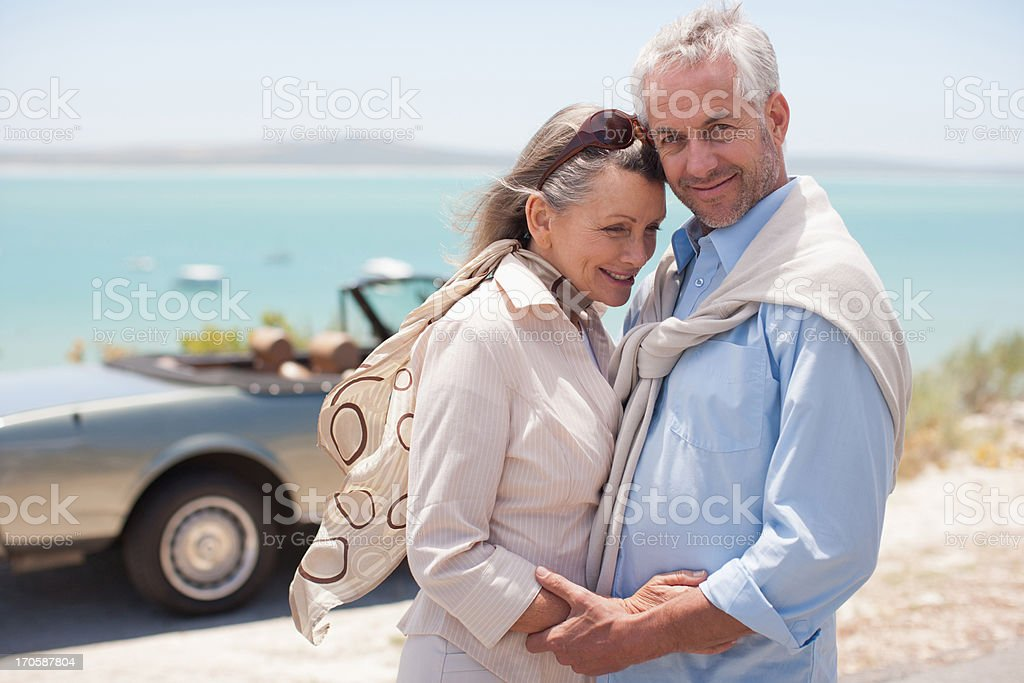 Mature couple hugging at waterfront royalty-free stock photo