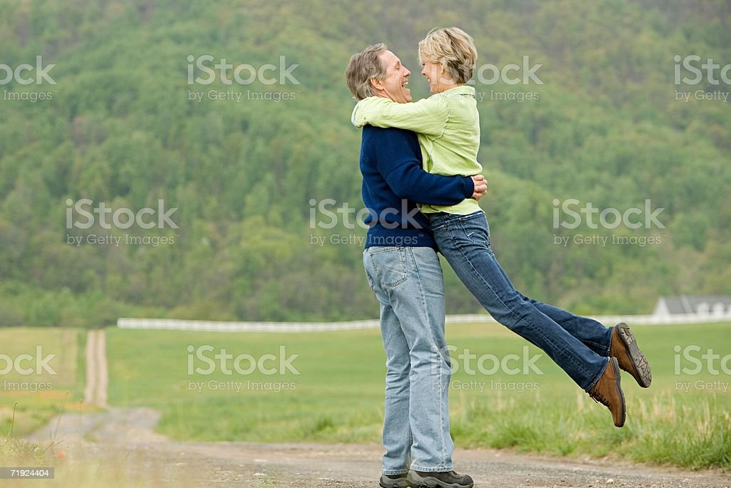 Mature couple hugging in a field royalty-free stock photo