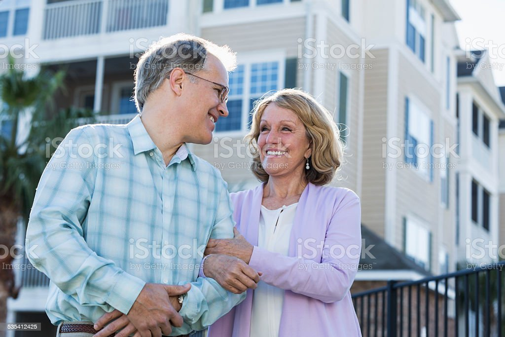 Mature couple in front of apartment building stock photo