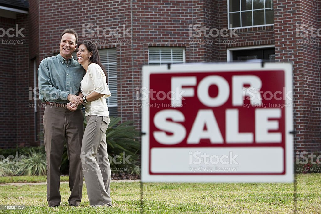Mature couple in front of home for sale stock photo