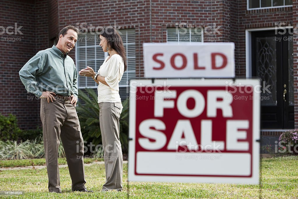 Mature couple in front of house with SOLD sign stock photo