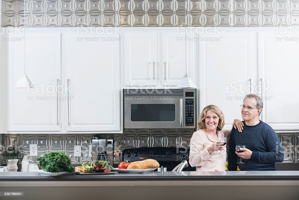 Mature couple in kitchen drinking red wine stock photo