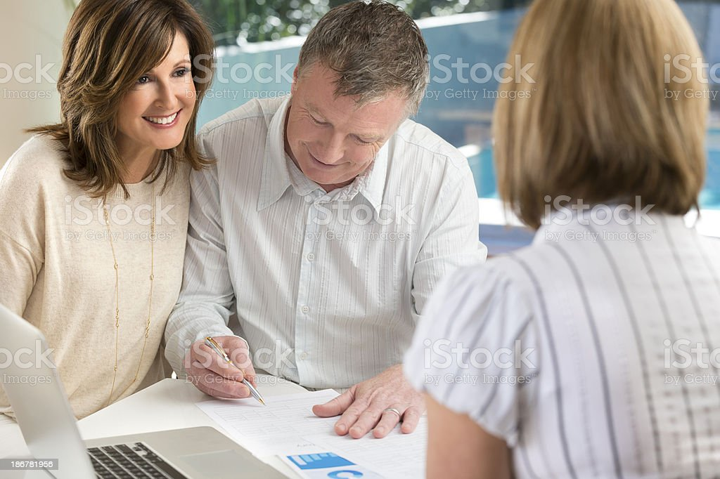 Mature Couple in Meeting signing contract with Advisor royalty-free stock photo
