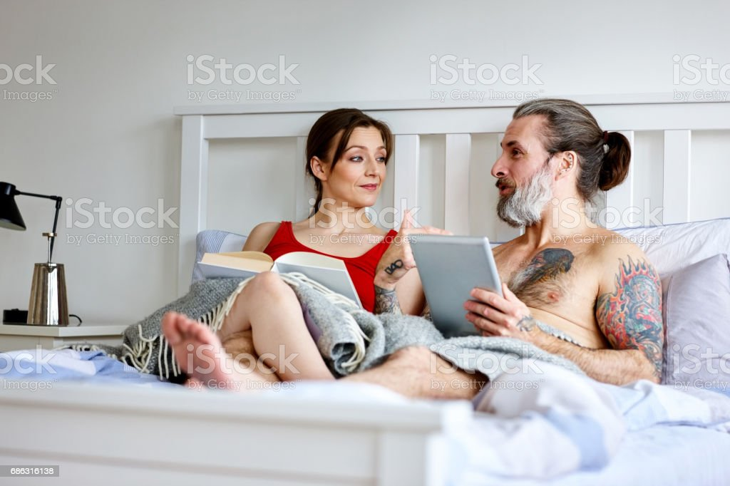 Mature couple interacting with each other on bed stock photo