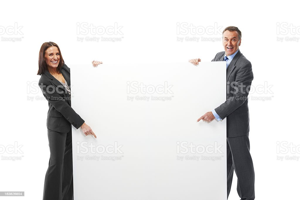 Mature couple isolated on white background pointing at board royalty-free stock photo