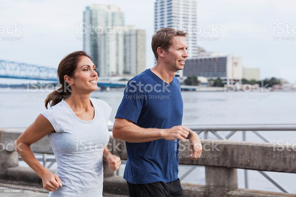 Mature couple jogging together along waterfront stock photo