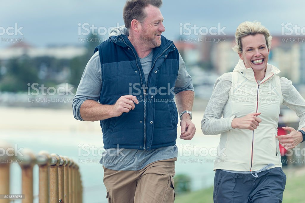 Mature couple jogging together. stock photo