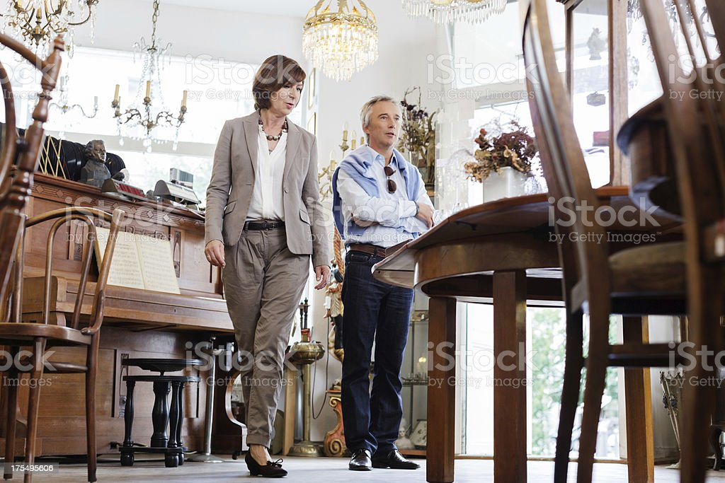 Mature couple looking at antiques in antique store stock photo
