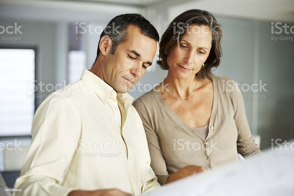Mature couple looking at building plan royalty-free stock photo