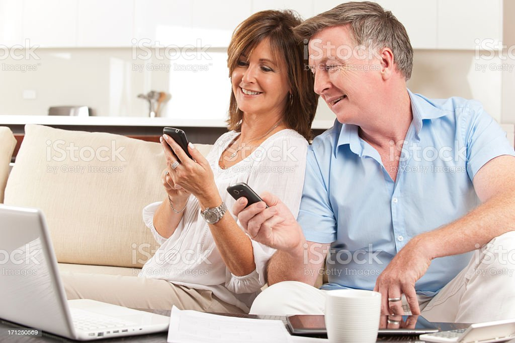 Mature Couple looking at each others mobile phones royalty-free stock photo