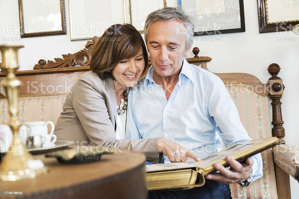 Mature Couple Looking At Old Photos stock photo