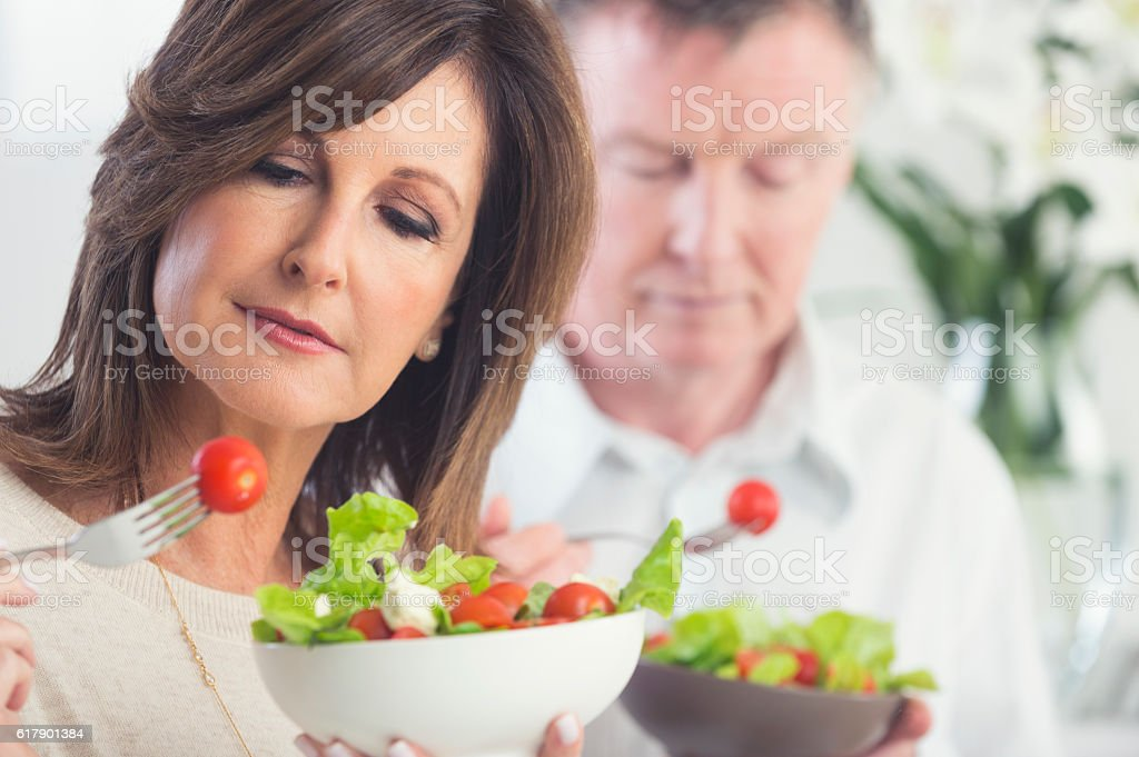 Mature couple looking worried about food stock photo
