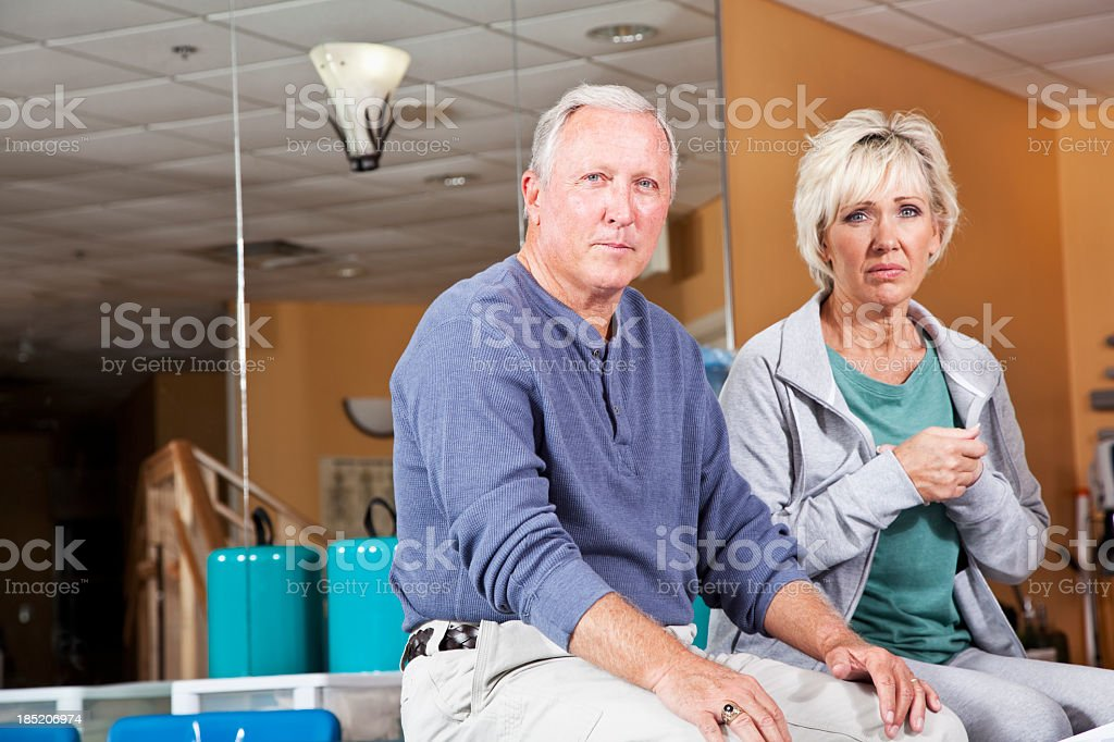 Mature couple looking worried in physical therapy clinic stock photo