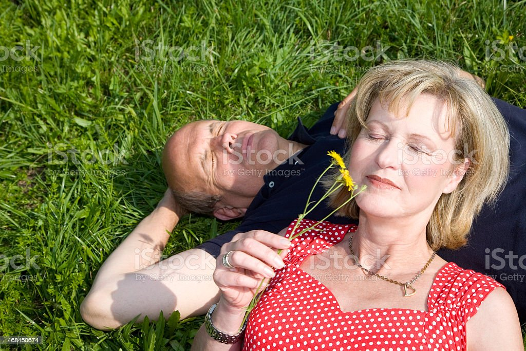 Mature couple lying in meadow stock photo