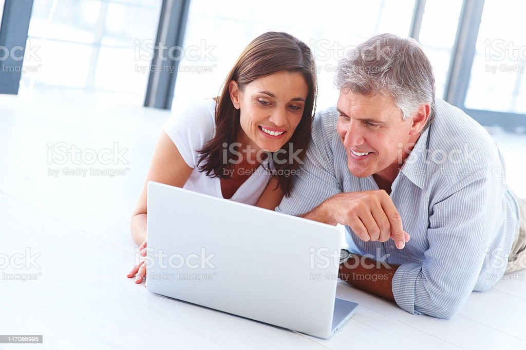 Mature couple lying on floor and using a laptop royalty-free stock photo