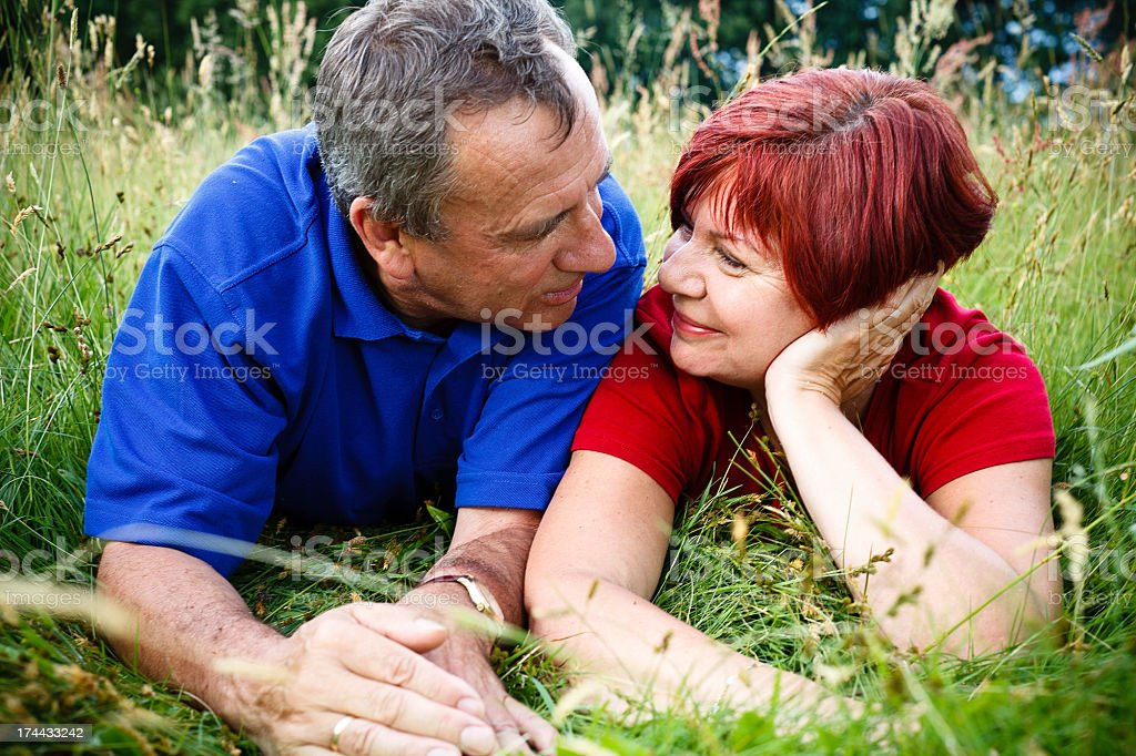 Mature Couple Lying on Grass Looking at Each Other royalty-free stock photo