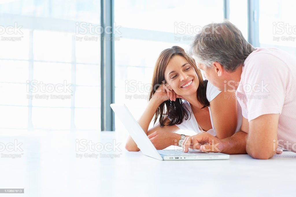 Mature couple lying on the floor at home and working on a laptop stock photo