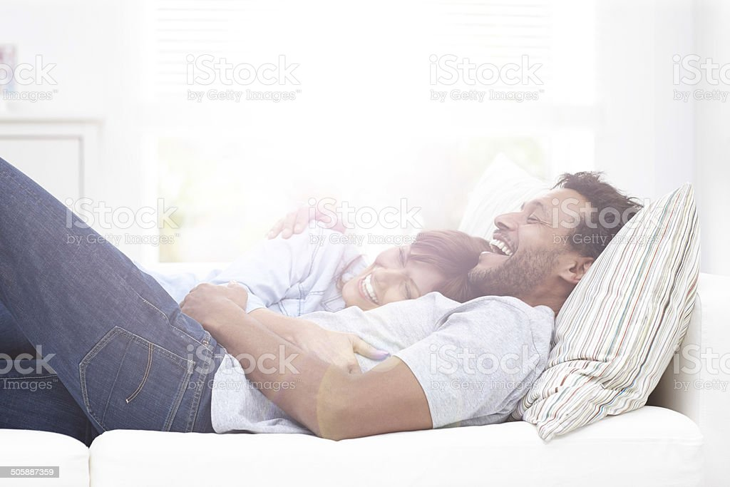 Mature couple lying together on couch smiling stock photo