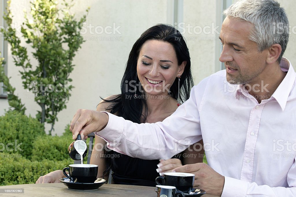 Mature couple. Man pouring cream into cup of coffee royalty-free stock photo