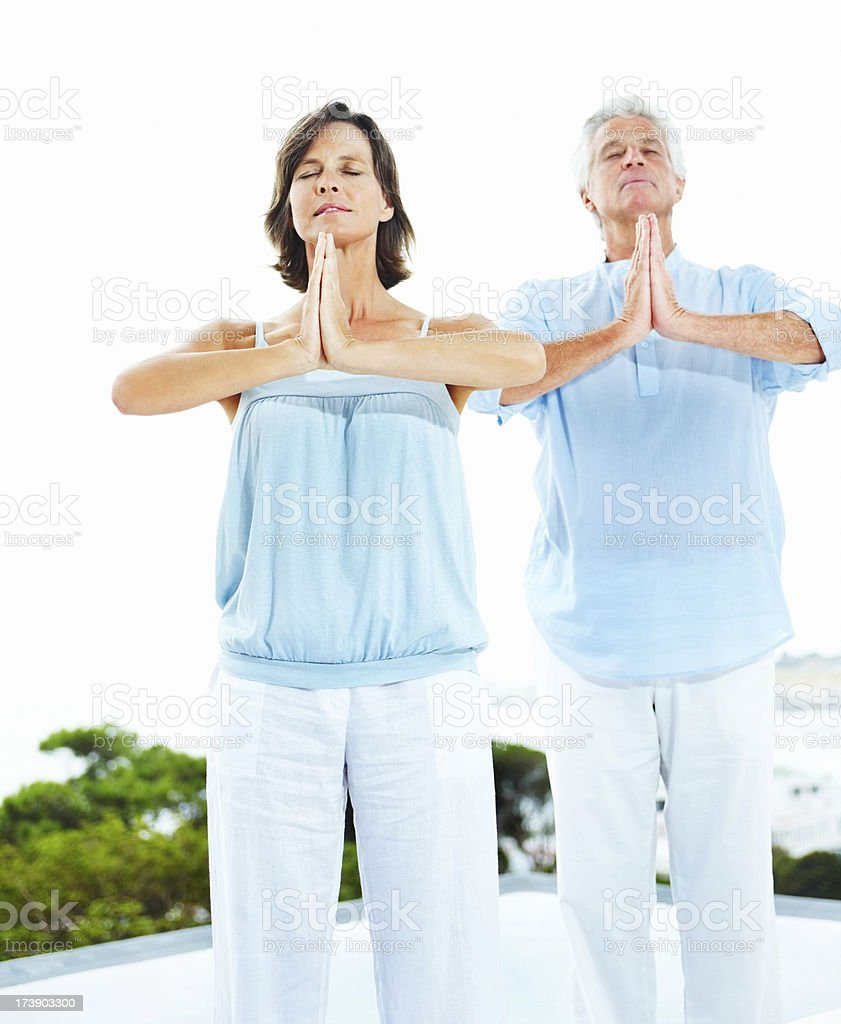 Mature couple meditating in prayer position royalty-free stock photo
