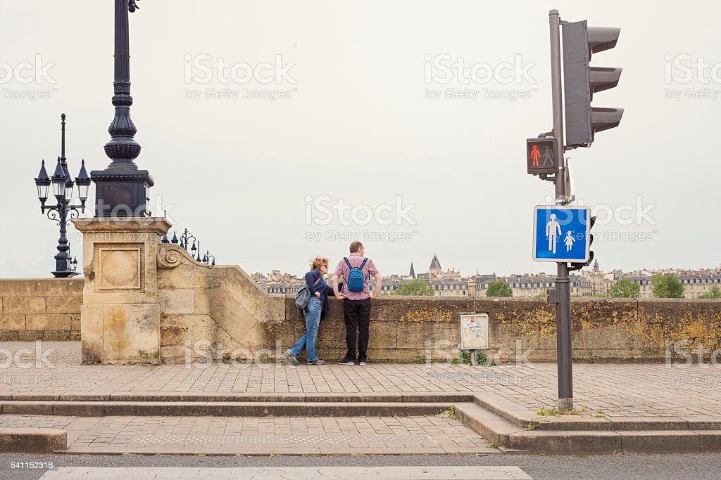 Mature couple of tourists looking at the view on bridge. stock photo