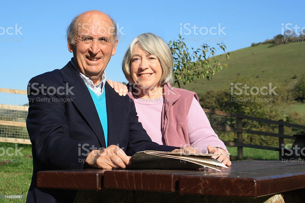 Mature couple on a bench with countryside royalty-free stock photo