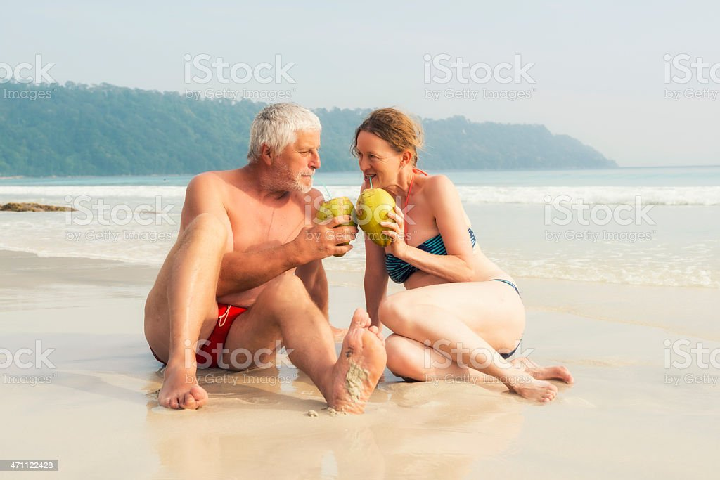 Mature couple on the beach with coconuts stock photo