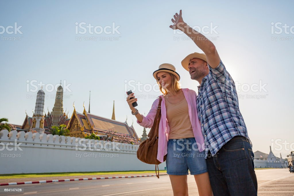 Mature Couple on Vacation in Thailand Using a Phone App To Catch a Taxi stock photo