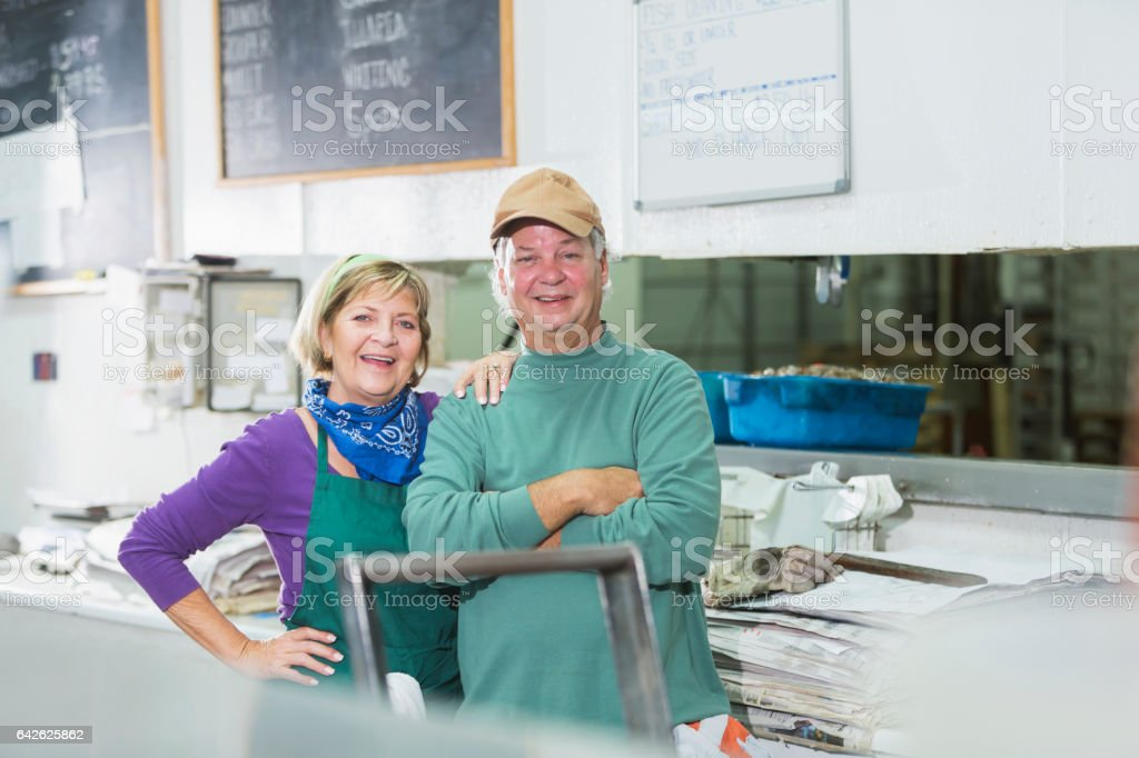 Mature couple, owners of fish market stock photo