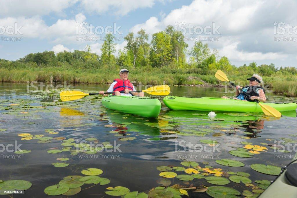 Mature couple paddles past lilypads stock photo