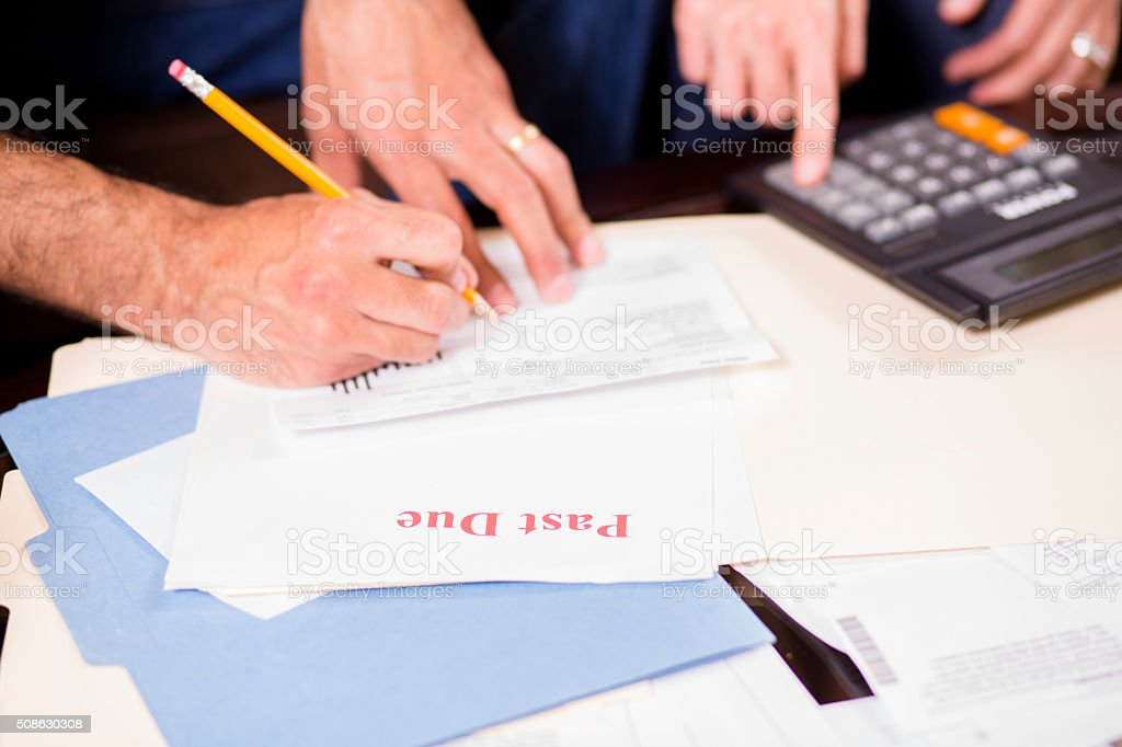 Mature couple paying monthly bills at home. stock photo