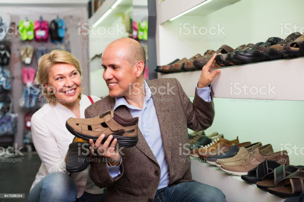 Mature couple picking men's sandals in shop stock photo