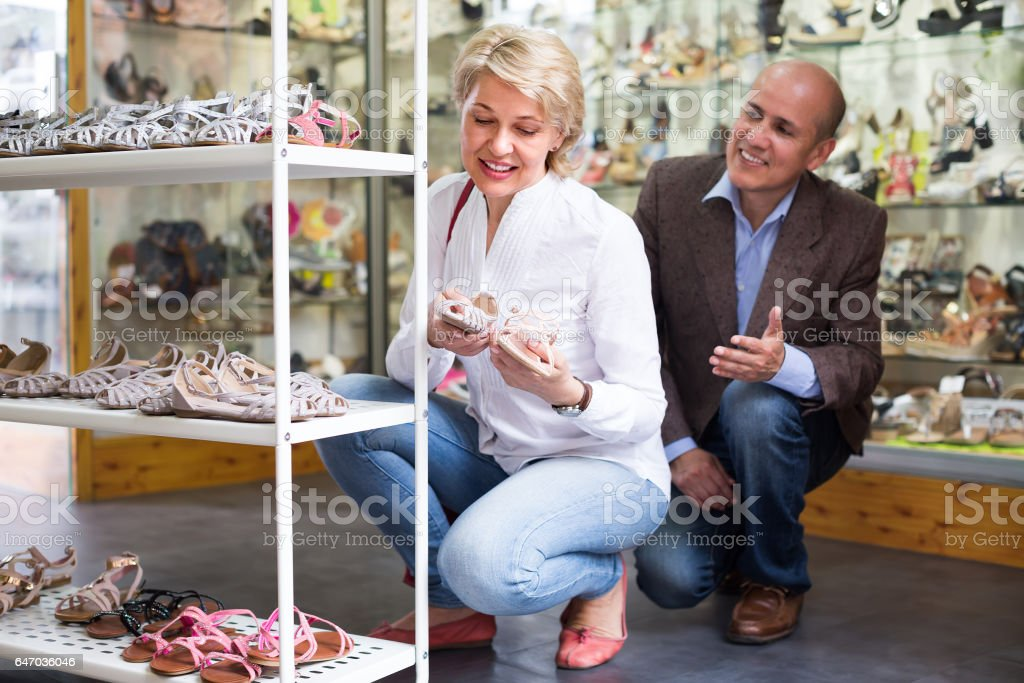 Mature couple picking shoes in boutique stock photo