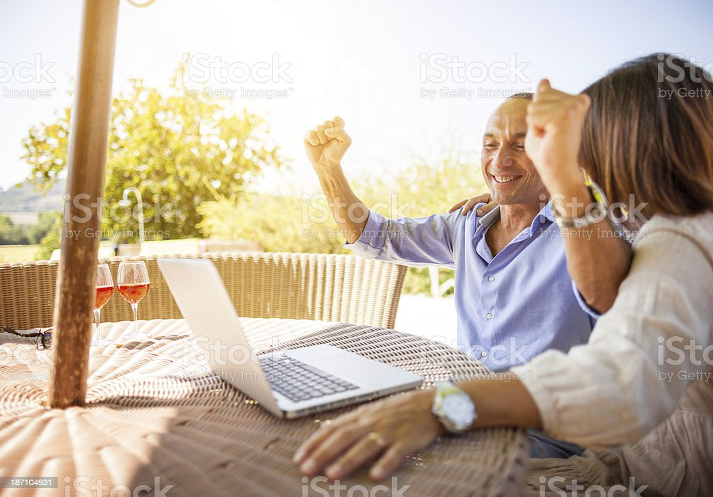 Mature couple planning vacation on laptop royalty-free stock photo