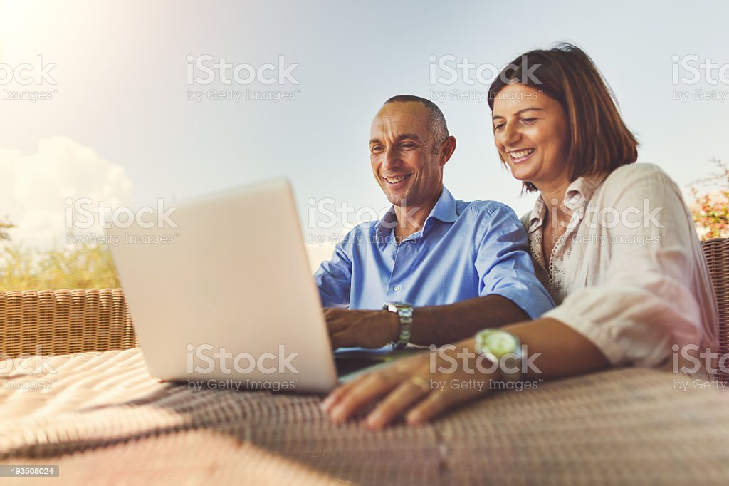 Mature couple planning vacation on laptop stock photo