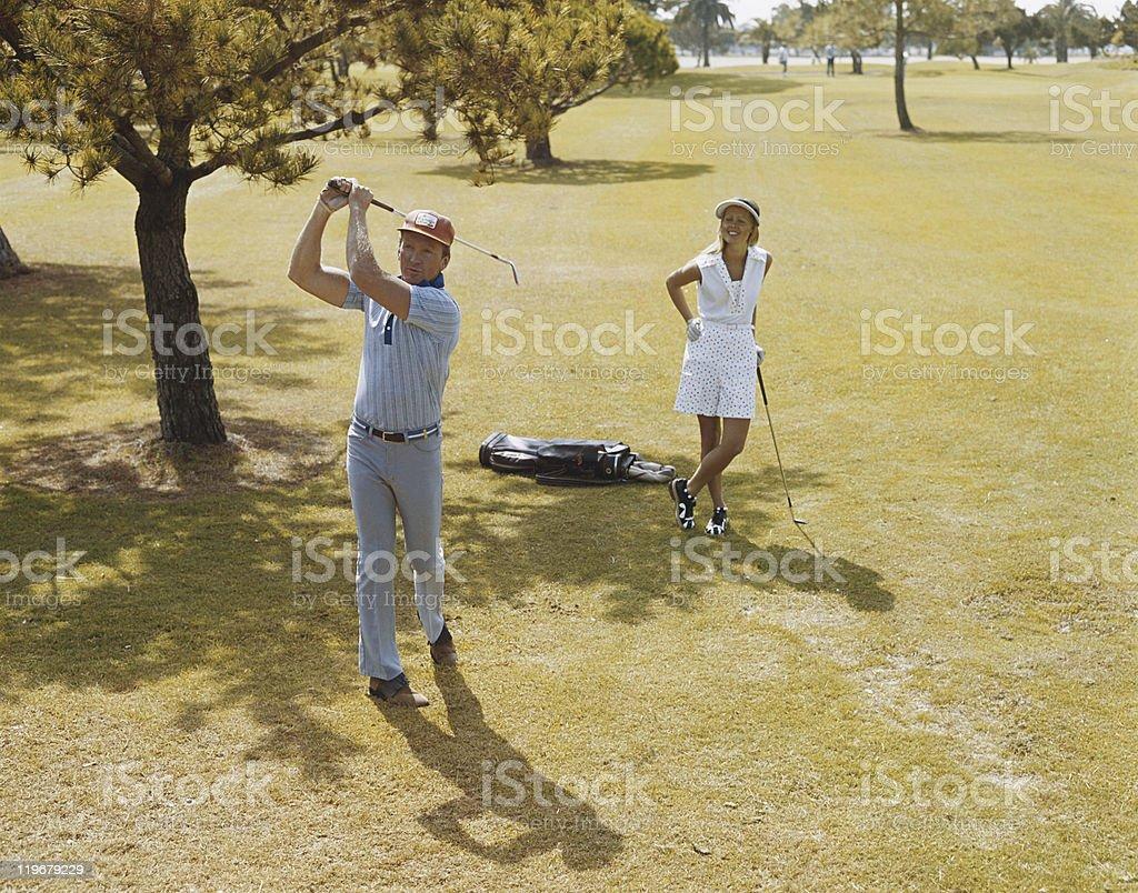 Mature couple playing golf, man swinging golf club stock photo