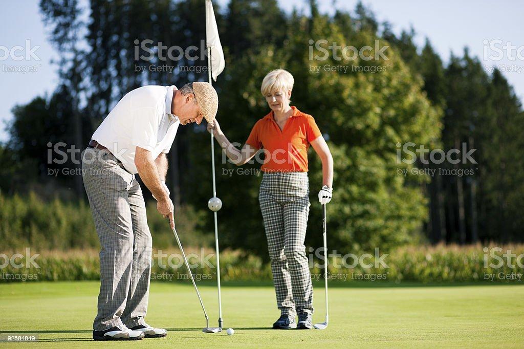 Mature couple playing Golf stock photo
