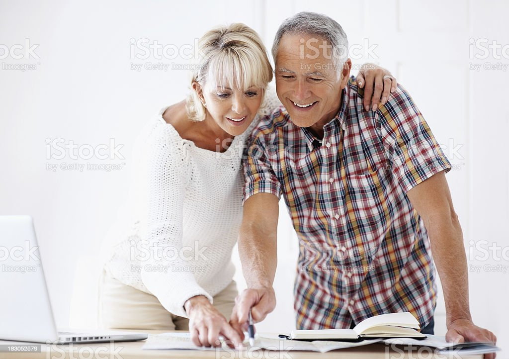 Mature couple pointing on map while planning their vacation royalty-free stock photo