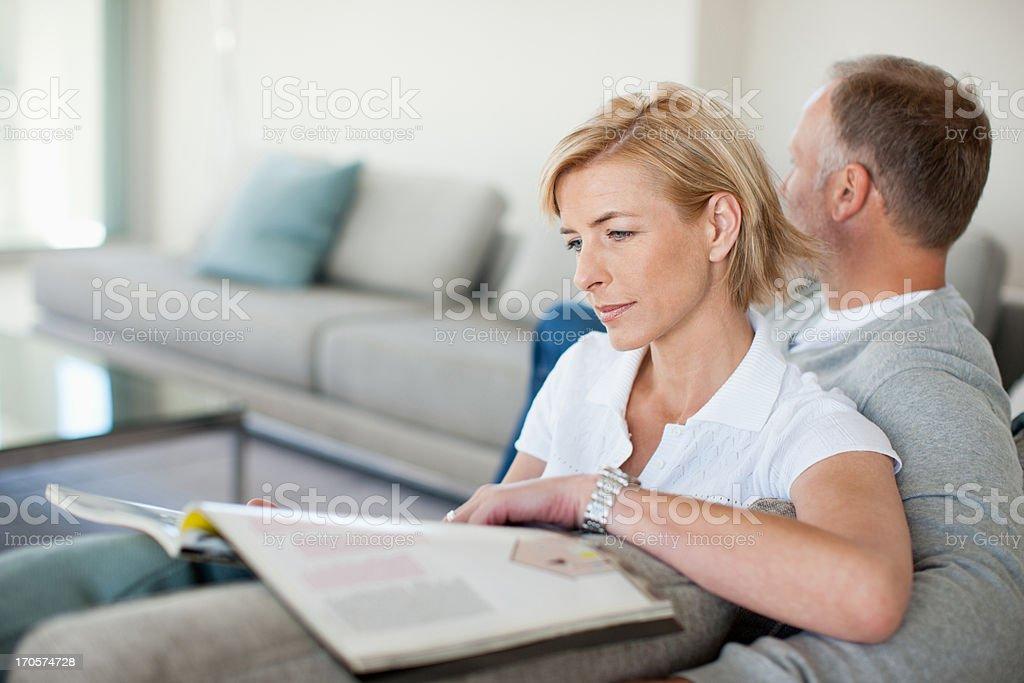 Mature couple reading on sofa royalty-free stock photo