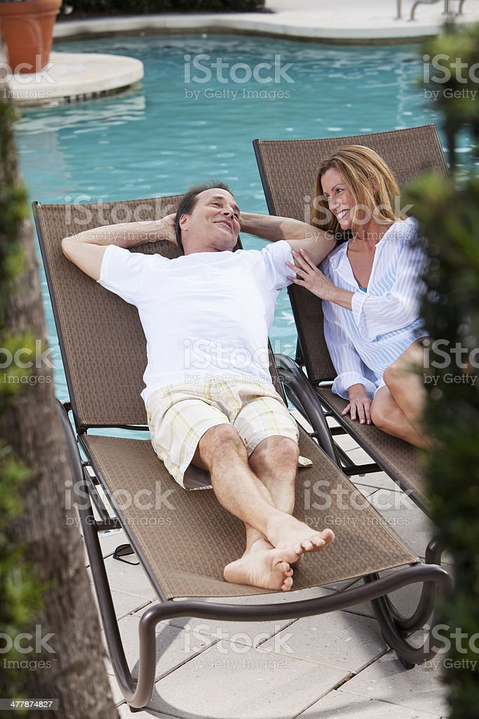 Mature couple relaxing by pool royalty-free stock photo