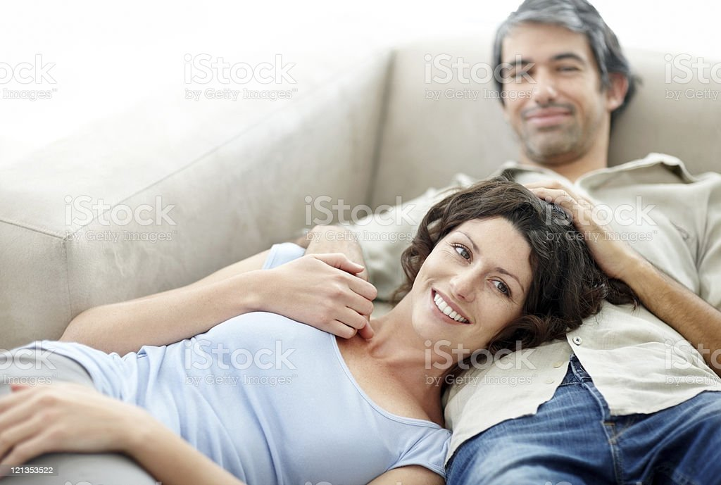 Mature couple relaxing on couch and smiling royalty-free stock photo