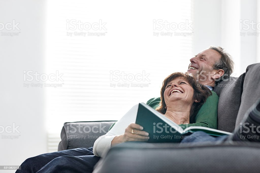 Mature couple relaxing on sofa with a book stock photo