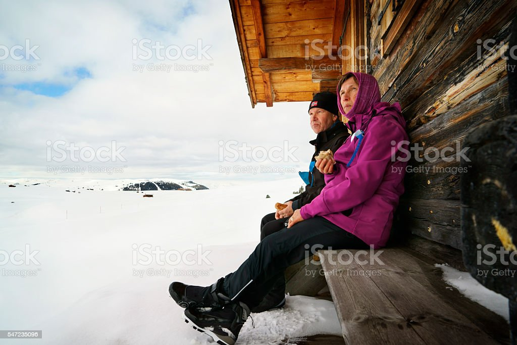 mature couple resting on bench in snow covered winter landscape stock photo