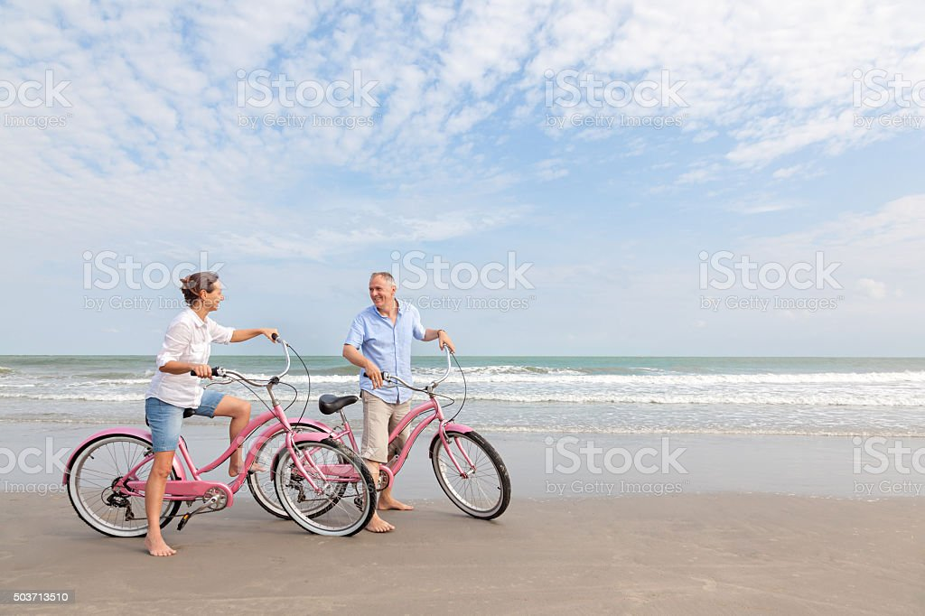 Mature couple riding bikes outdoors on beach at sunset stock photo
